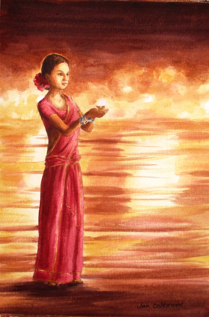 Young woman offering a lit candle to the Ganges.